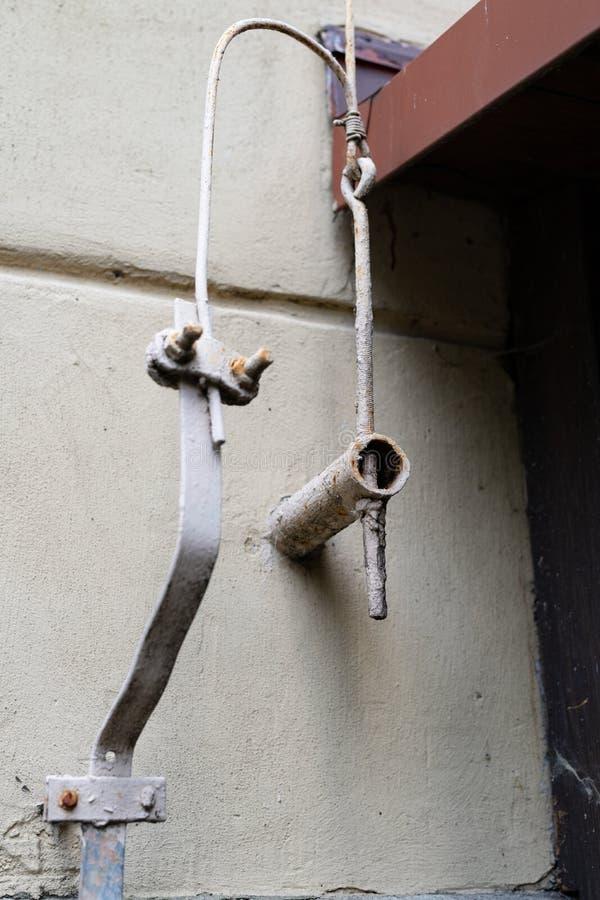 Oude bliksembescherming in een losgemaakt huis De kabels van de bliksembescherming stock afbeelding
