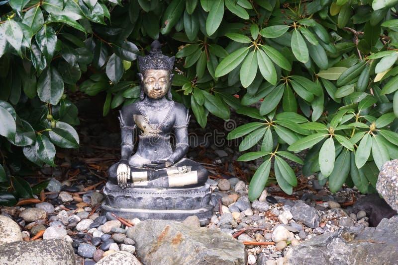 Oude boeddha-sculptuur zit onder de groene bladgroen royalty-vrije stock afbeelding