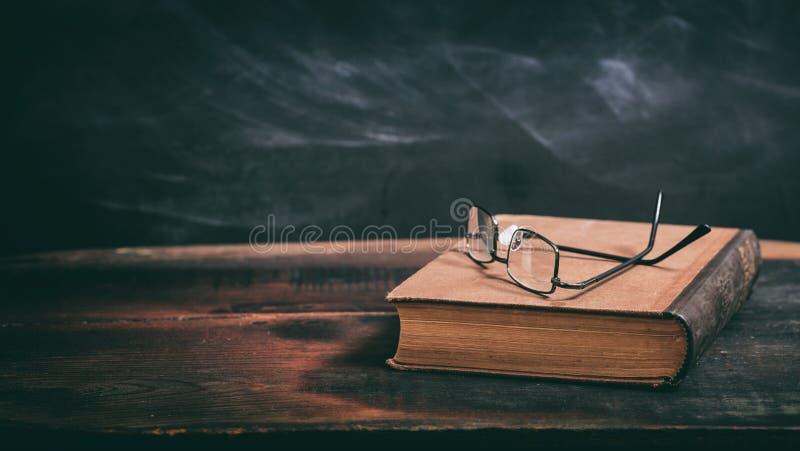 Oude boek en oogglazen op bordachtergrond royalty-vrije stock afbeeldingen