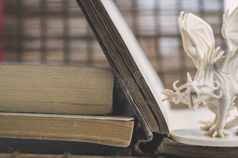 Oude boeken en een plastic cijfer van een fantasiedraak stock afbeeldingen