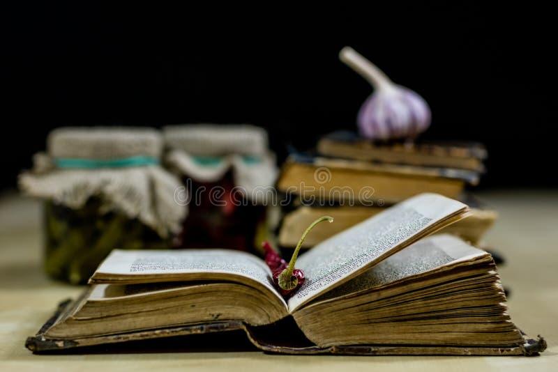 Oude boeken en kruiden Droge peper en recepten Oude keukenlijst stock foto's