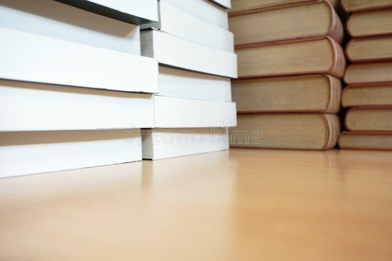 Oude boeken en nieuwe die boeken omhoog op het houten bureau worden gestapeld royalty-vrije stock fotografie