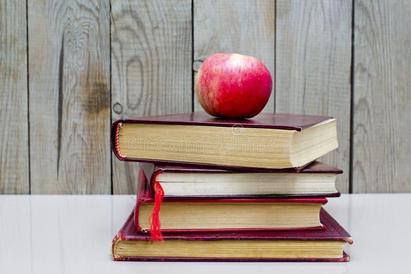 Oude boeken met appel op een witte achtergrond stock foto's