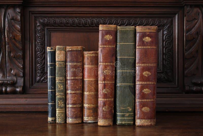 Oude boeken op een antiek houten meubilair stock foto's
