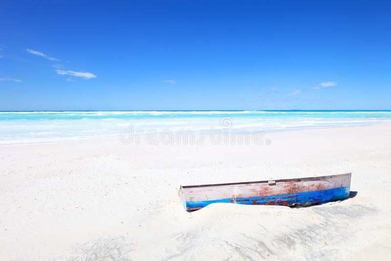 Oude boot op wit tropisch strand en blauwe hemel royalty-vrije stock afbeeldingen