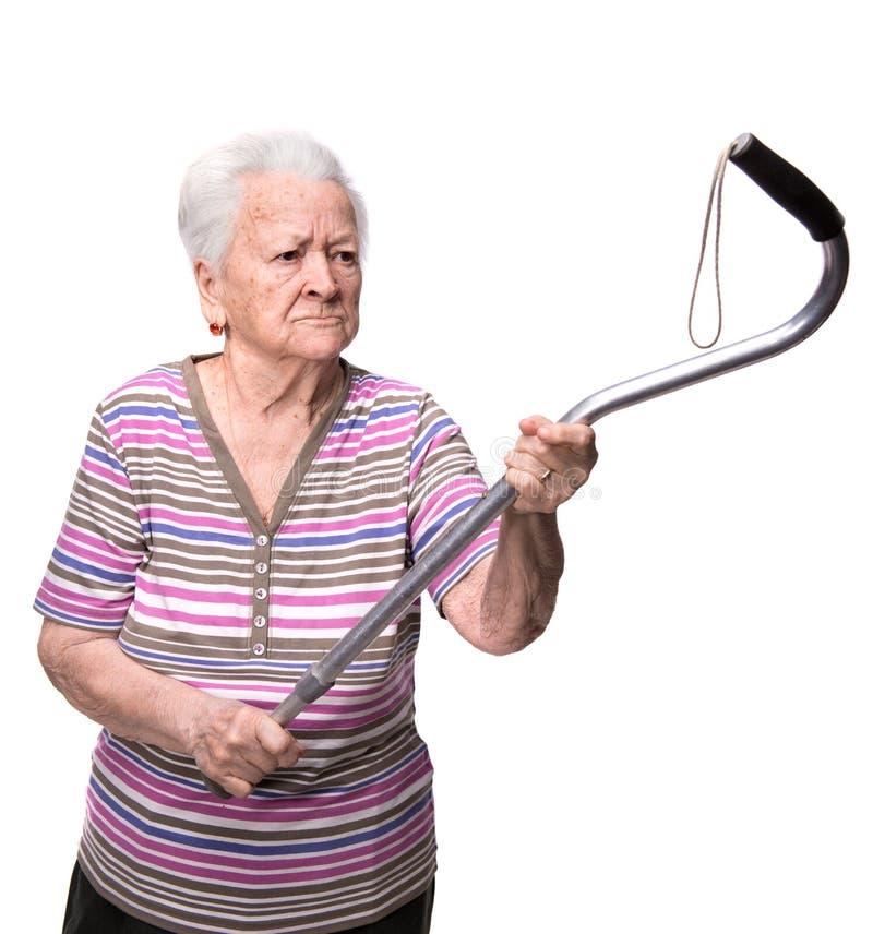 Oude boze vrouw die met een riet dreigen stock foto's