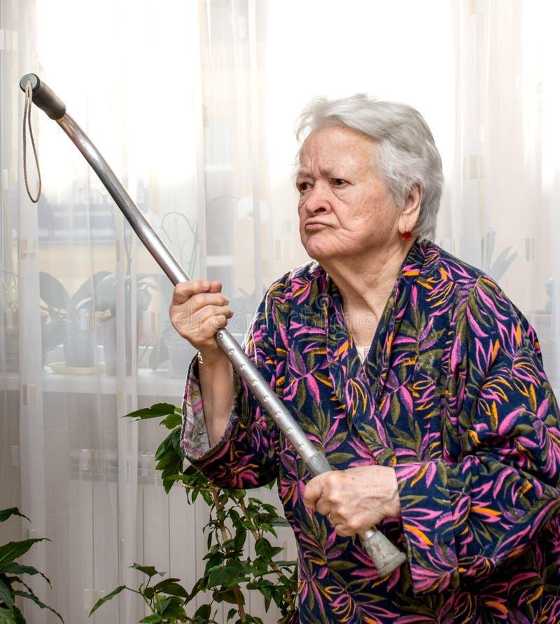 Oude boze vrouw die met een riet dreigen royalty-vrije stock fotografie