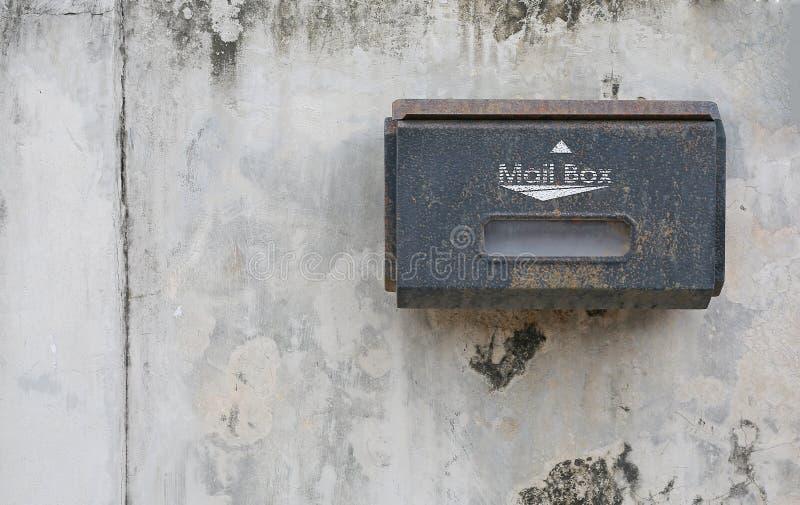 Oude brievenbus opgezet op een cementmuur met exemplaarruimte stock foto