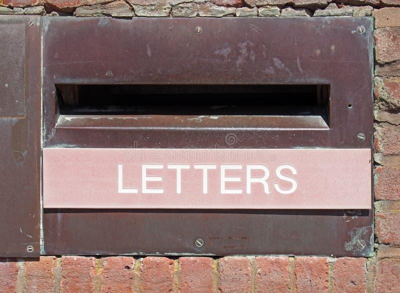 Oude Britse postbrievenbus in een bakstenen muur met geroeste metaalrand en de woordbrieven op een langzaam verdwenen rood paneel stock afbeeldingen