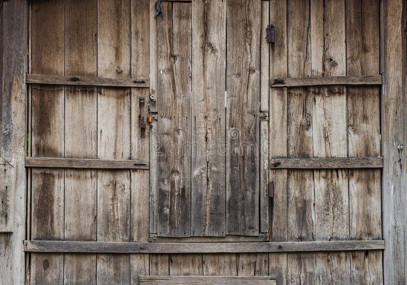 Oude bruine houten deur ingebed in leeftijden houten muur stock foto's