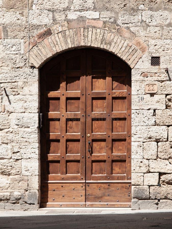 Oude bruine houten deur in middeleeuwse straat stock afbeeldingen