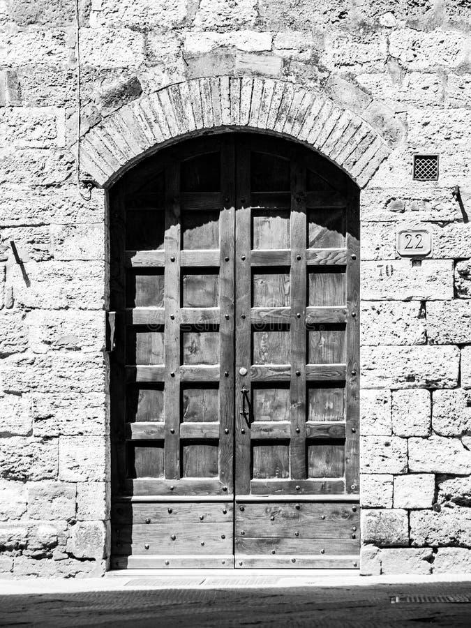 Oude bruine houten deur in middeleeuwse straat stock fotografie