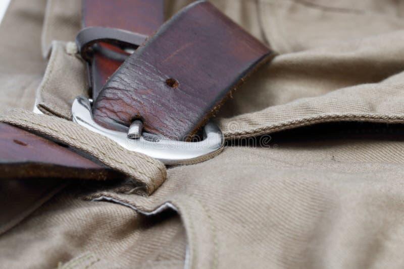 Oude bruine riem met jeans stock afbeeldingen