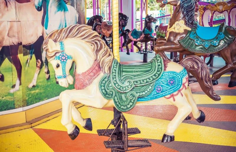 Oude carrousel in een vakantiepark Drie paarden en vliegtuig op een traditionele kermisterrein uitstekende carrousel stock afbeelding