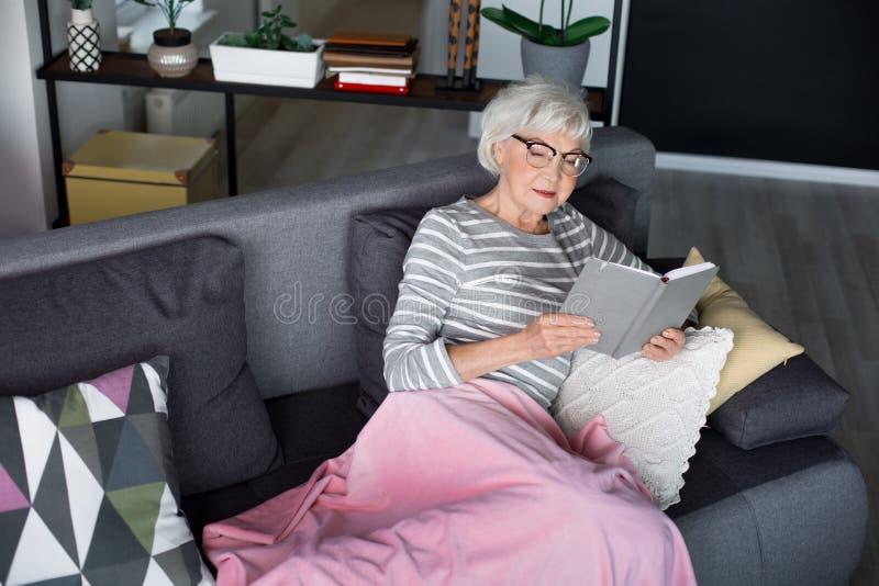Oude charmante vrouw die op bank met notitieboekje rusten royalty-vrije stock afbeeldingen