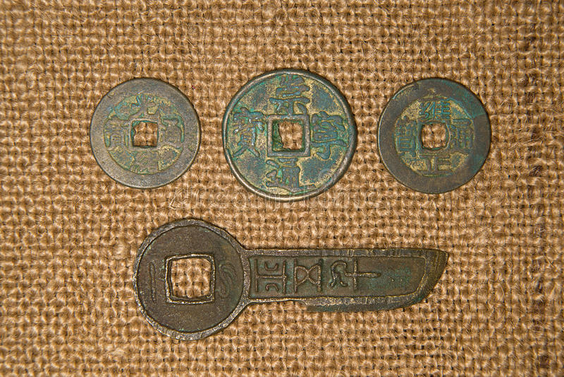 Oude Chinese bronsmuntstukken op oude doek stock foto's