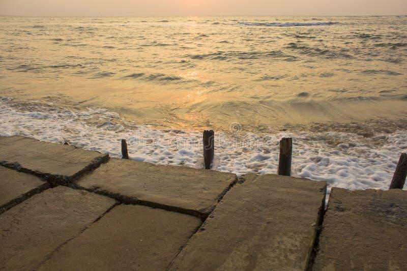 Oude concrete dijk met het plakken van vernietigde houten omheiningen tegen de achtergrond van overzeese golven tijdens zonsonder stock afbeeldingen