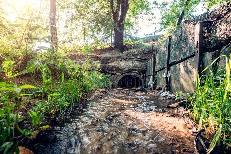 Oude concrete drainagepijpen met stromende afvalwater, riolerings of rioleringstunnelbuis met waterstroom royalty-vrije stock afbeelding
