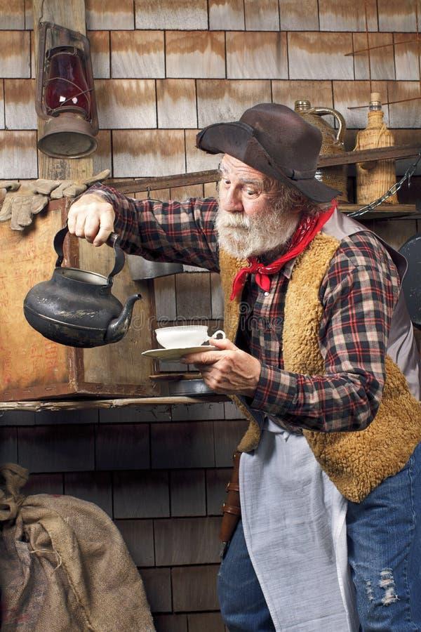Oude cowboy met ketel en de theekop van China stock afbeeldingen