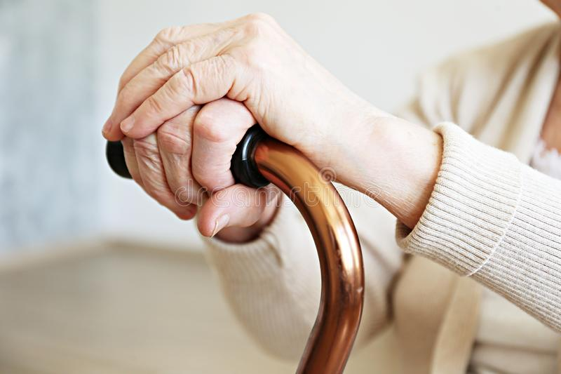 Oude dagvrouw met gezondheidsproblemen die haar wapens rusten bij het lopen van riet royalty-vrije stock foto