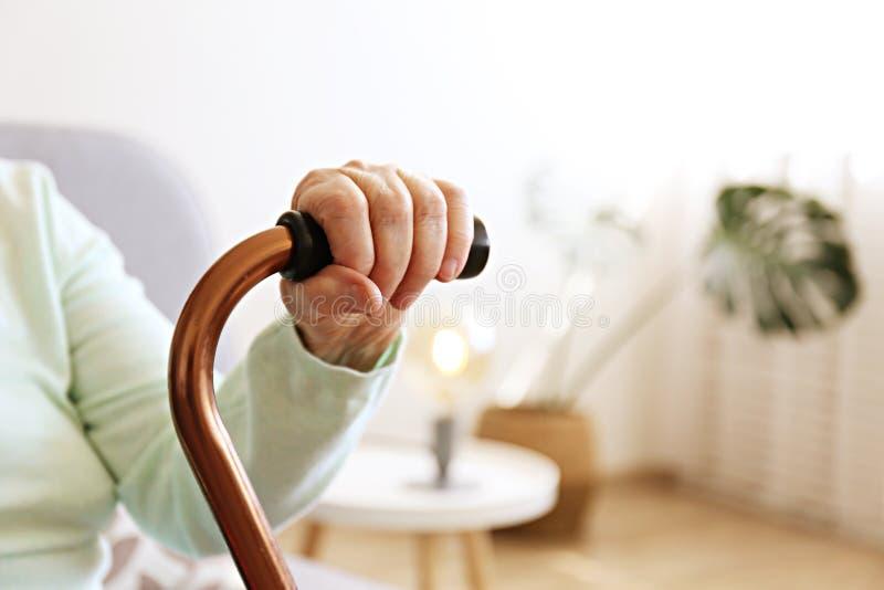Oude dagvrouw met gezondheidsproblemen die haar wapens rusten bij het lopen van riet stock afbeelding