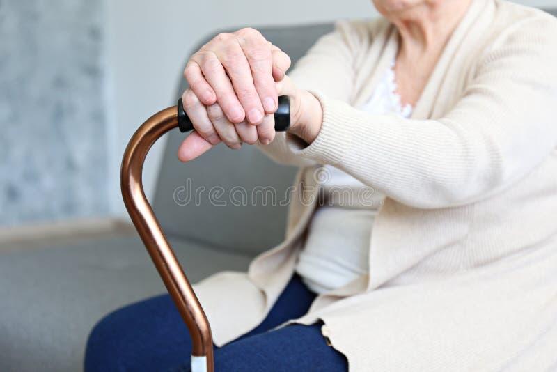 Oude dagvrouw met gezondheidsproblemen die haar wapens rusten bij het lopen van riet stock afbeeldingen