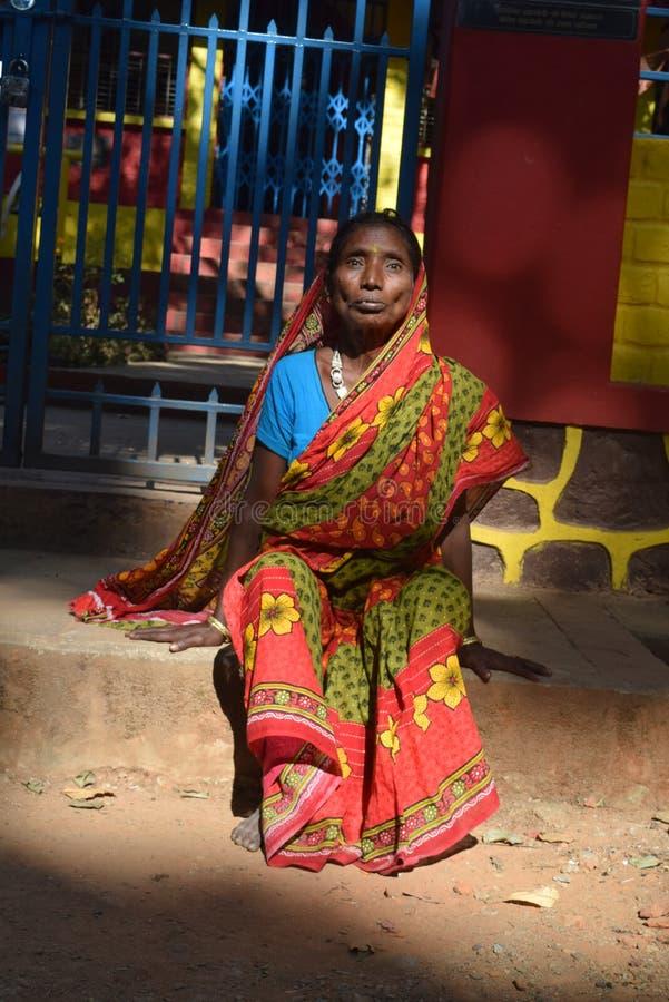 Oude dame die dichtbij tempelpoort wordt gesitueerd royalty-vrije stock fotografie