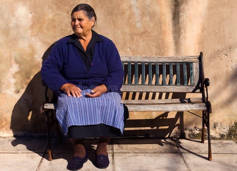 Oude dame in een Grieks dorp stock foto's