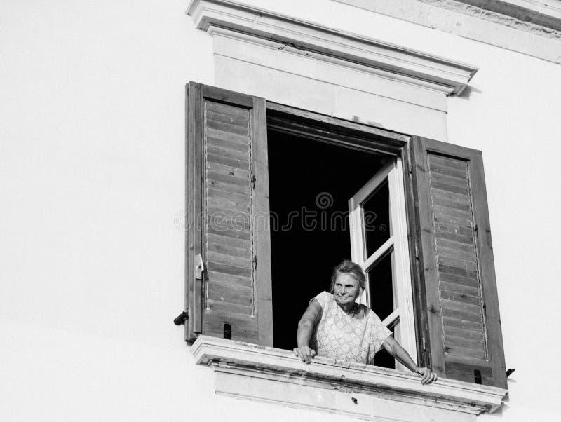 Oude dame lettende op toeristen en voetgangers van haar venster royalty-vrije stock foto's