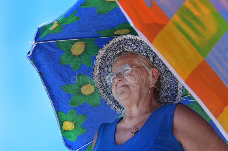 Oude dame met hoed tussen twee sunshades royalty-vrije stock afbeelding