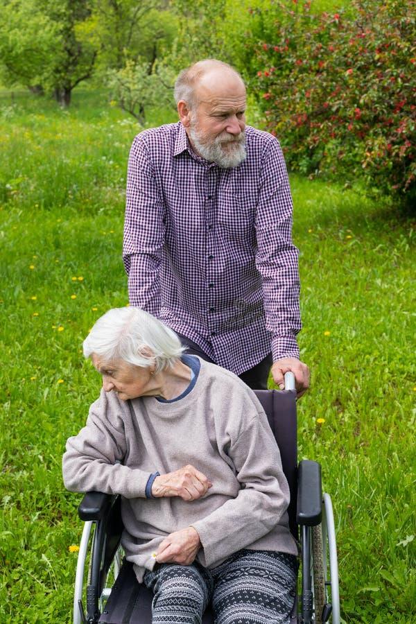Oude dame met zwakzinnigheid in een rolstoel en een werker uit de hulpverlening stock afbeeldingen