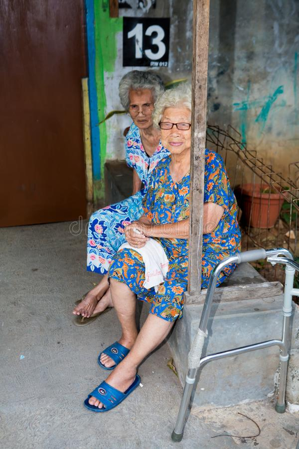 Oude dames in een krottenwijk in Djakarta stock afbeeldingen
