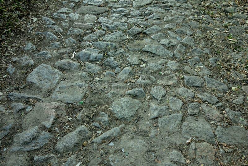 Oude de bestratingsweg van de bloksteen Verlaten vuile oppervlakte met doorstane het bedekken plakken en stofgrond tussen stock foto