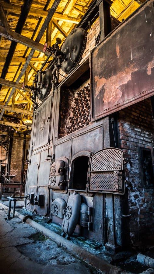Oude de industriële steenkoolopen haard van de stoommotor met gele achtergrond stock foto's