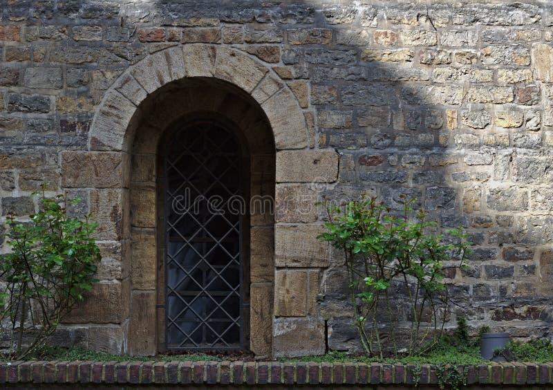 Oude in de schaduw gestelde steenmuur met groene installaties, versperd venster en flard van zonlicht stock foto
