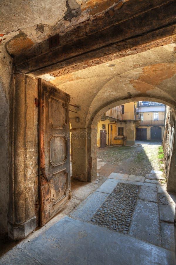 Oude deur en kleine werf in Saluzzo, Italië. stock afbeelding