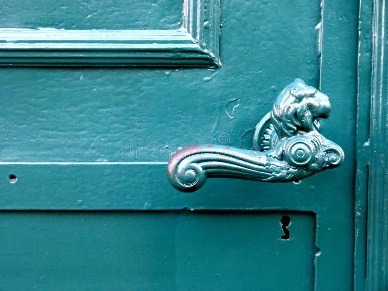Oude deur met listig deurhandvat met het hoofd van de leeuw stock afbeelding