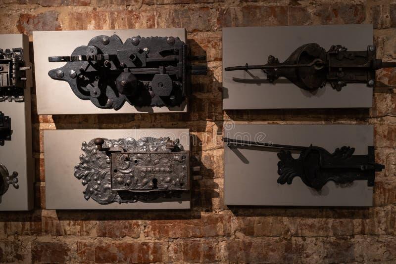 Oude deurgaten en handvatten - Houten die ingang op bakstenen muren - Handvatten van metaal worden gemaakt stock foto