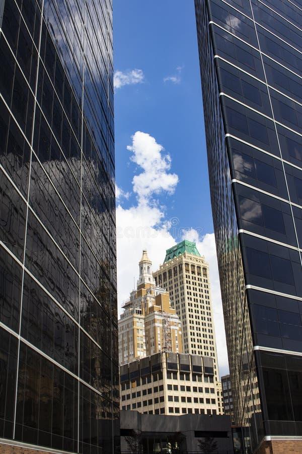Oude die art decogebouwen tussen twee ultra moderne gebouwen onder blauwe hemel met wolken worden bekeken stock afbeeldingen