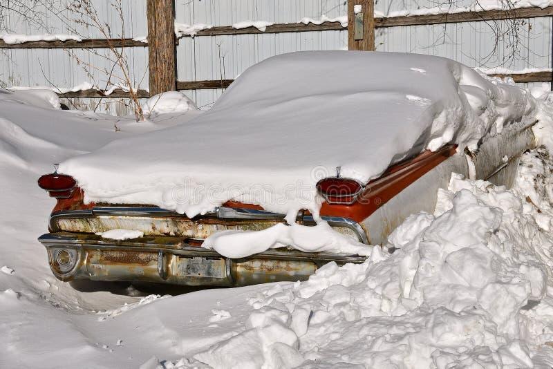 Oude die auto in een sneeuwbank wordt begraven stock afbeelding