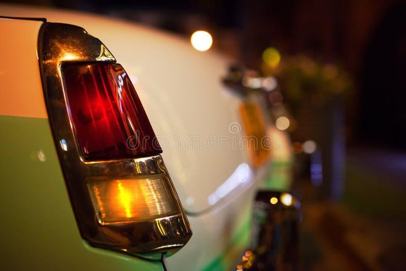 Oude die autokoplamp met nachtlichten door straatlantaarns worden verlicht stock afbeeldingen