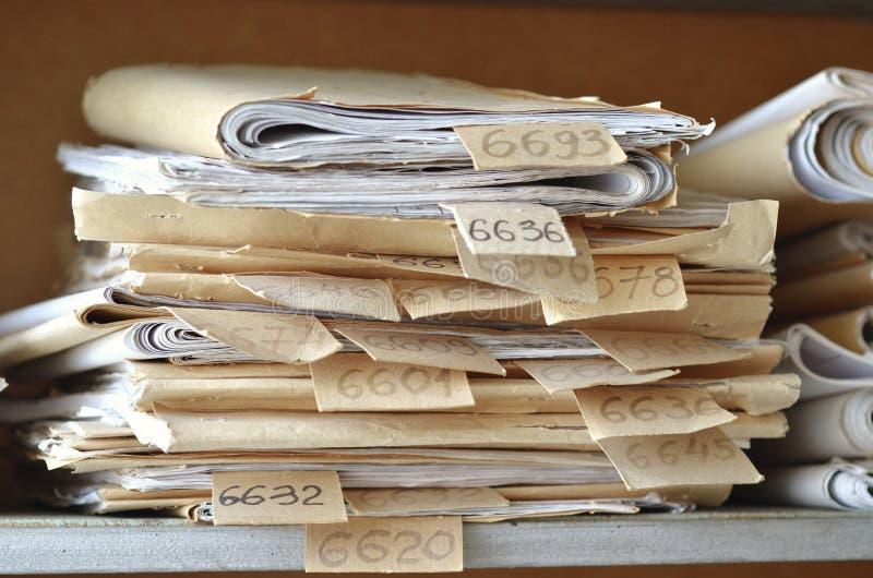 Oude die documenten, tekeningen met aantallen op planken in o worden gestapeld stock fotografie