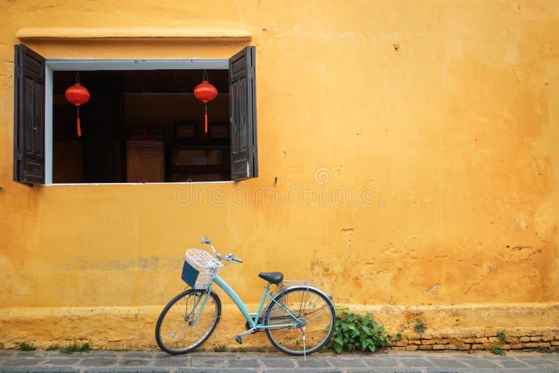 Oude die fiets dichtbij huismuur wordt geparkeerd stock afbeeldingen