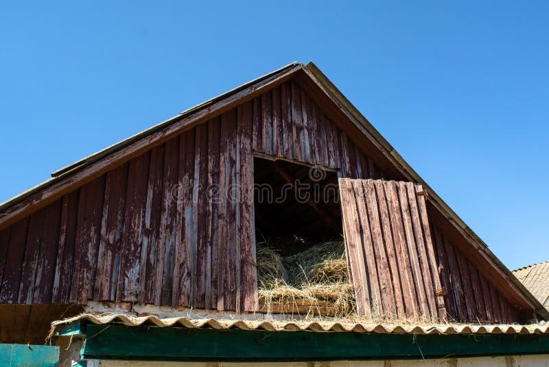 Oude die loods voor hooiopslag in het dorp wordt gevestigd royalty-vrije stock foto's