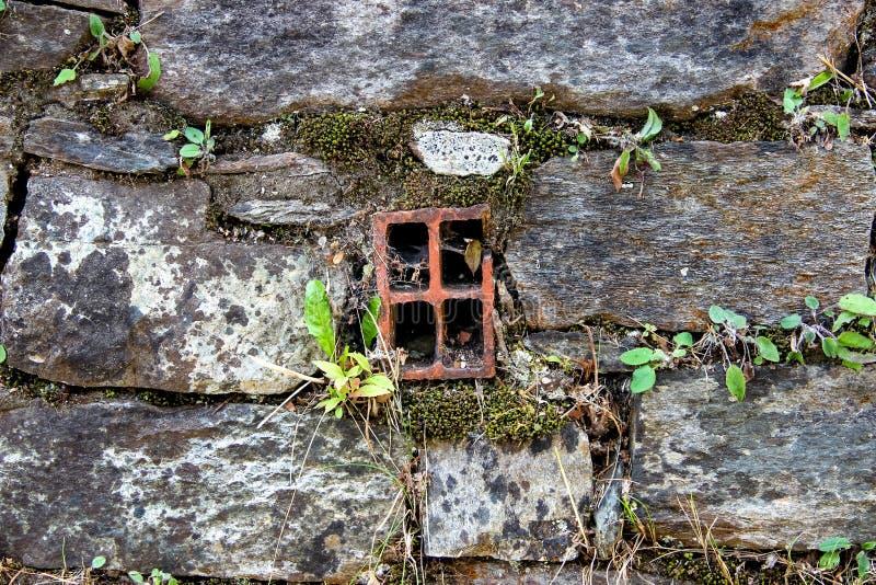 Oude die muur van natuurlijke rotsen met venster-als water-afvoerkanaal pijp in het centrum en met installaties en korstmossen tu royalty-vrije stock foto