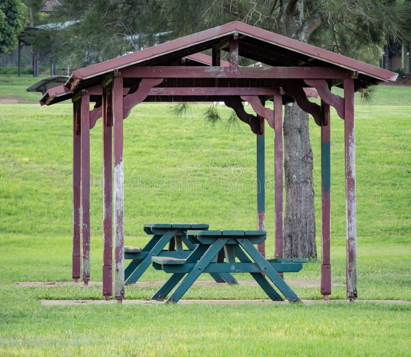 Oude die picknicklijsten door de structuur van de dakschuilplaats in park worden behandeld stock afbeelding