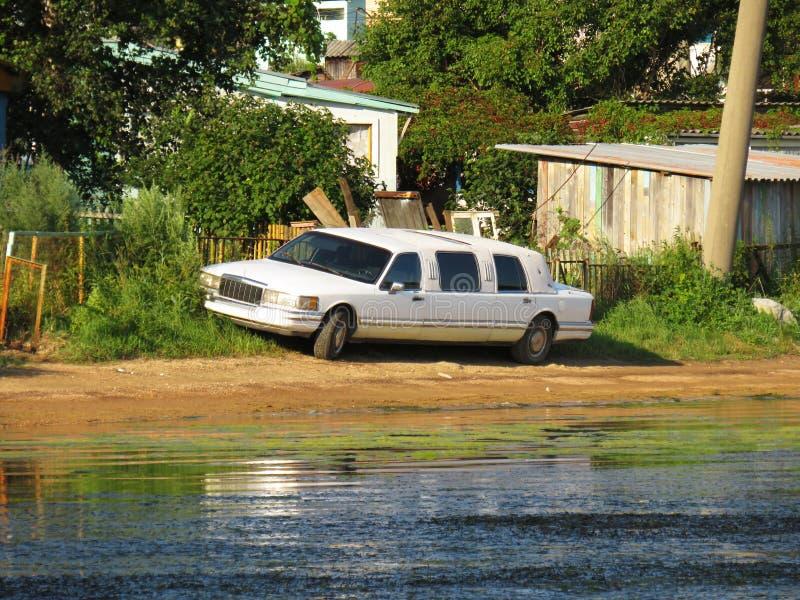 Oude die retro limousineauto dichtbij keten in struiken op het strand wordt geparkeerd royalty-vrije stock afbeelding