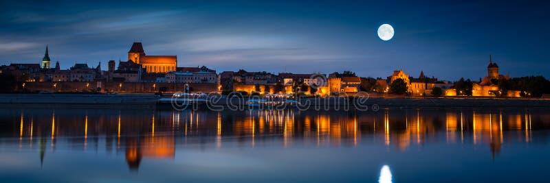 Oude die stad in rivier bij zonsondergang wordt weerspiegeld Torun stock fotografie