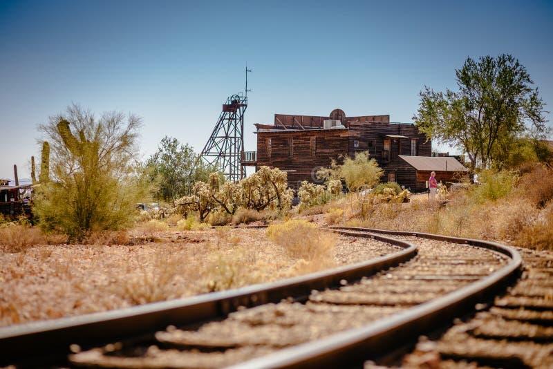 Oude die Treinsporen in de Spookstad van de Goudveldgoudmijn in Youngsberg, Arizona, de V.S. door woestijn worden omringd royalty-vrije stock fotografie