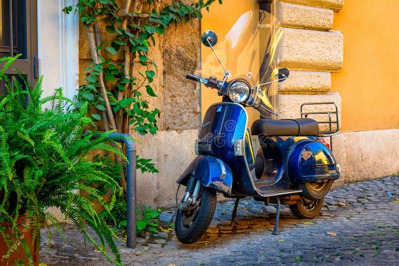 Oude die Vespa-autoped op oude straat in Rome, Italië wordt geparkeerd stock foto's